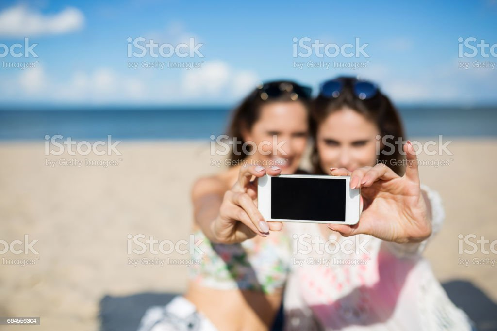 Two girls on beach taking selfie by smartphone royalty-free stock photo