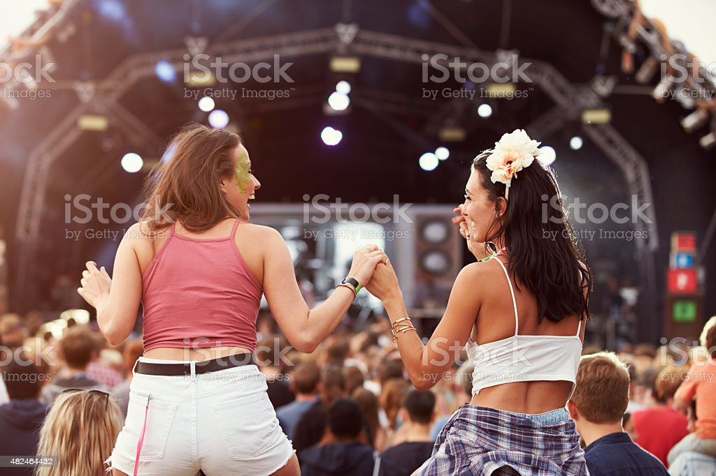 Two girls on shoulders in the crowd at music festival stock photo