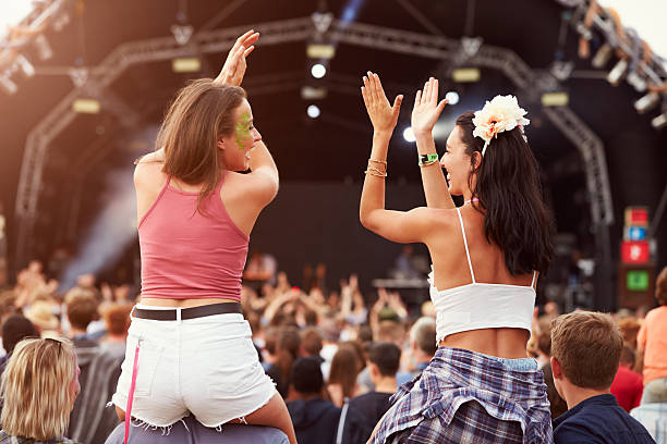 two girls on shoulders in the crowd at music festival - traditioneel festival stockfoto's en -beelden