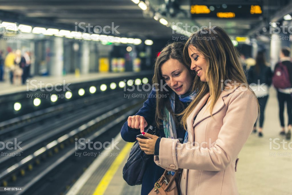 Two girls on the London underground waiting for the train. stock photo