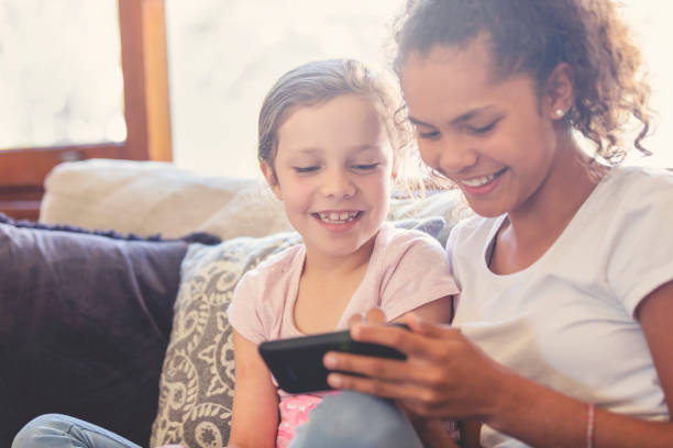 Zwei Mädchen auf dem Sofa, ein Smartphone zu betrachten. – Foto