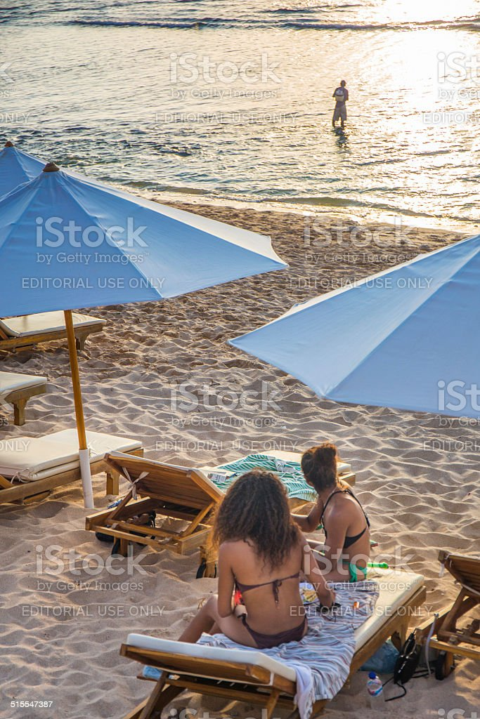 Two girls on under parasol in the beach stock photo