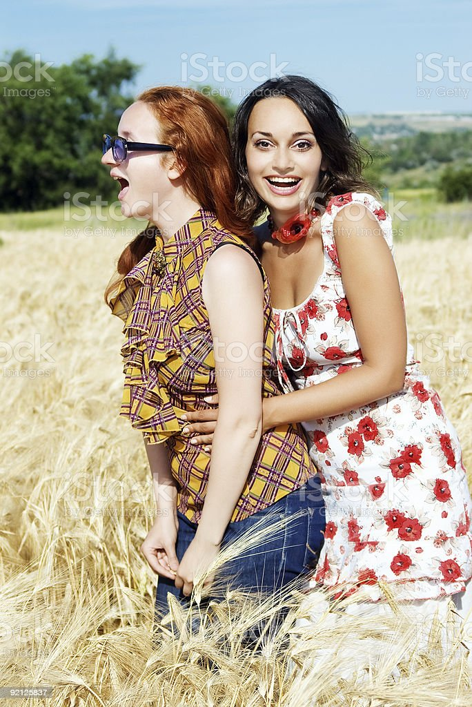 two girls on wheat field fooling around and laughing royalty-free stock photo