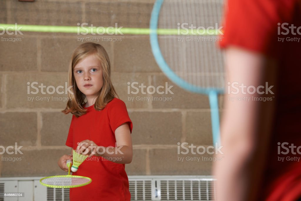 Two Girls Playing Badminton In School Gym stock photo