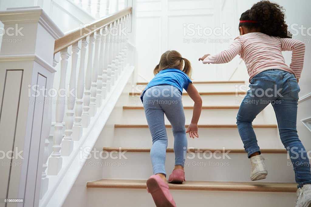 Two Girls Playing Game On Staircase At Home stock photo