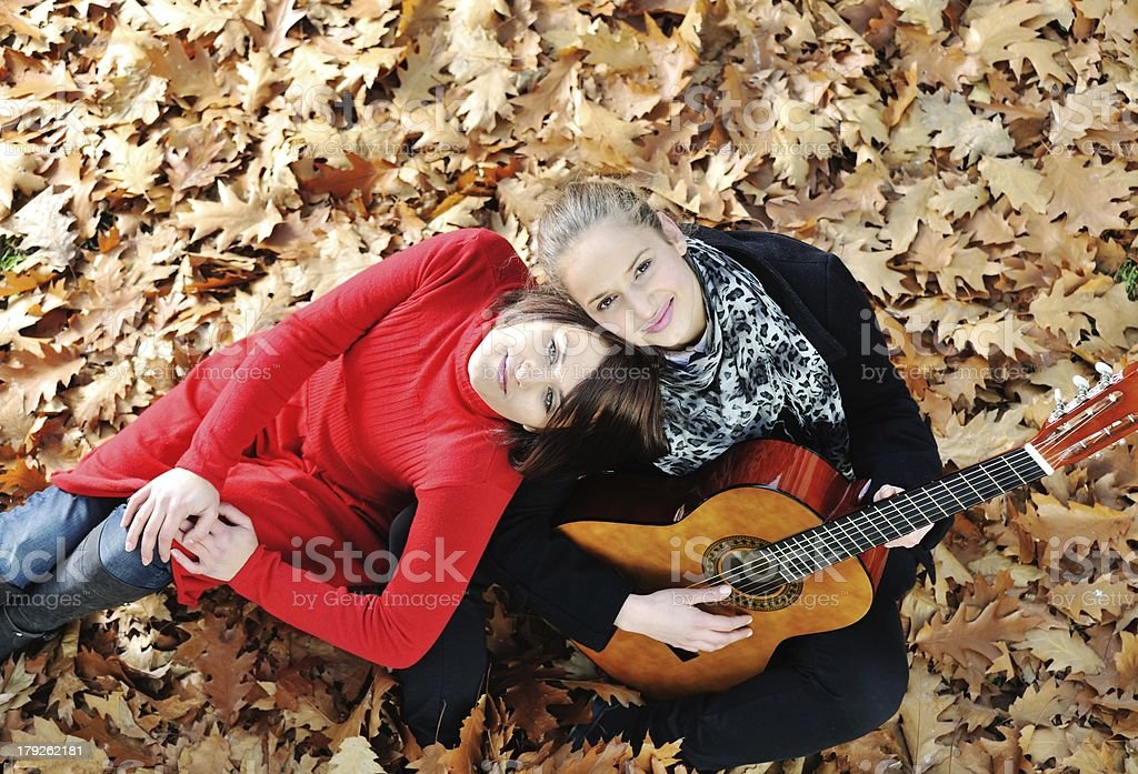Two girls playing guitar and having good time in nature royalty-free stock photo