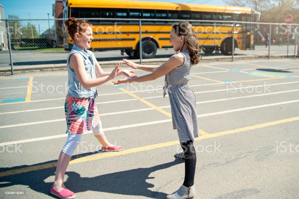 Two girls playing hand games in school playground at recess.. stock photo
