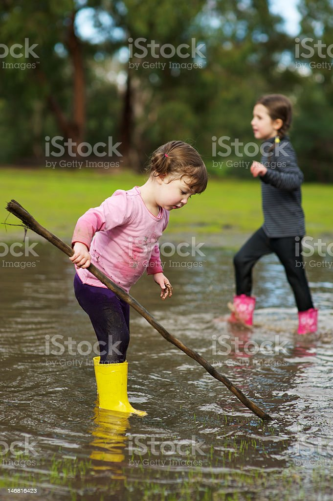Two girls playing in a big puddle royalty-free stock photo