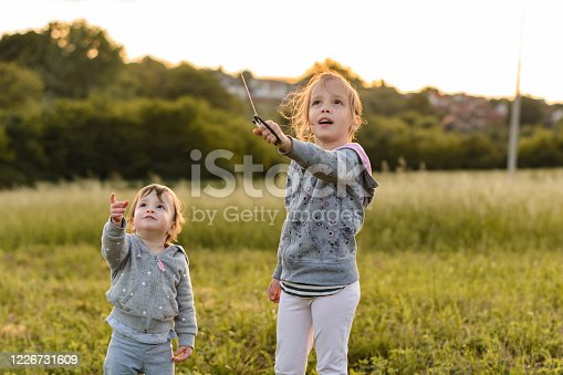 Two sisters playing whit kite outdoors