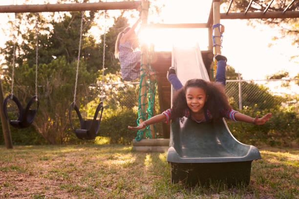 two girls playing outdoors at home on garden slide - sliding stock photos and pictures