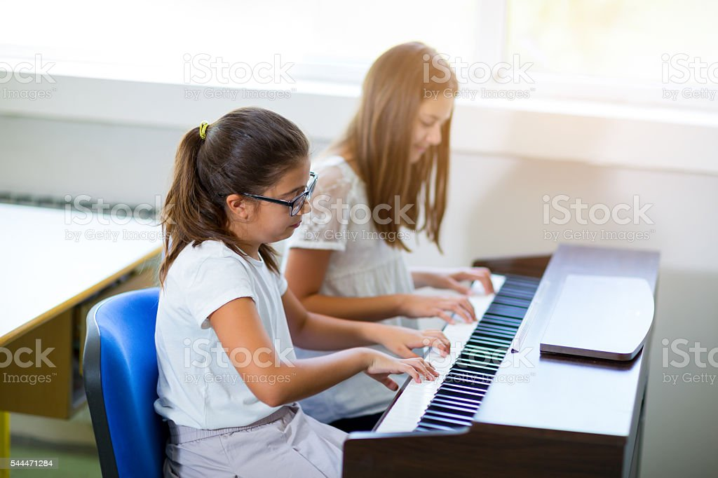 Two girls playing the piano at the music school stock photo