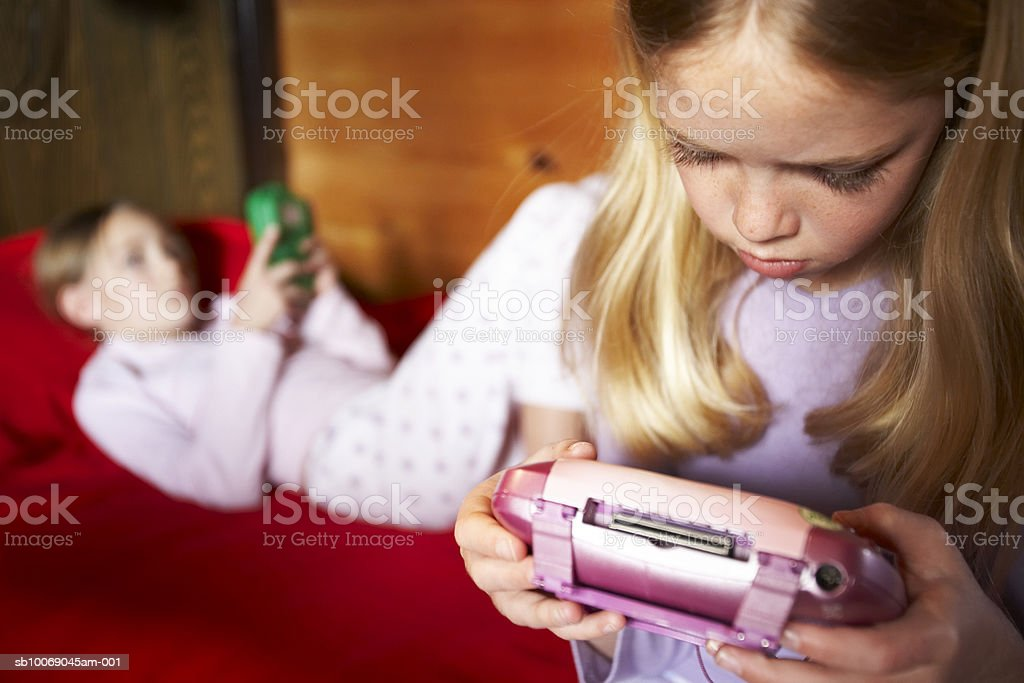 Two girls (6-11) playing video game 免版稅 stock photo