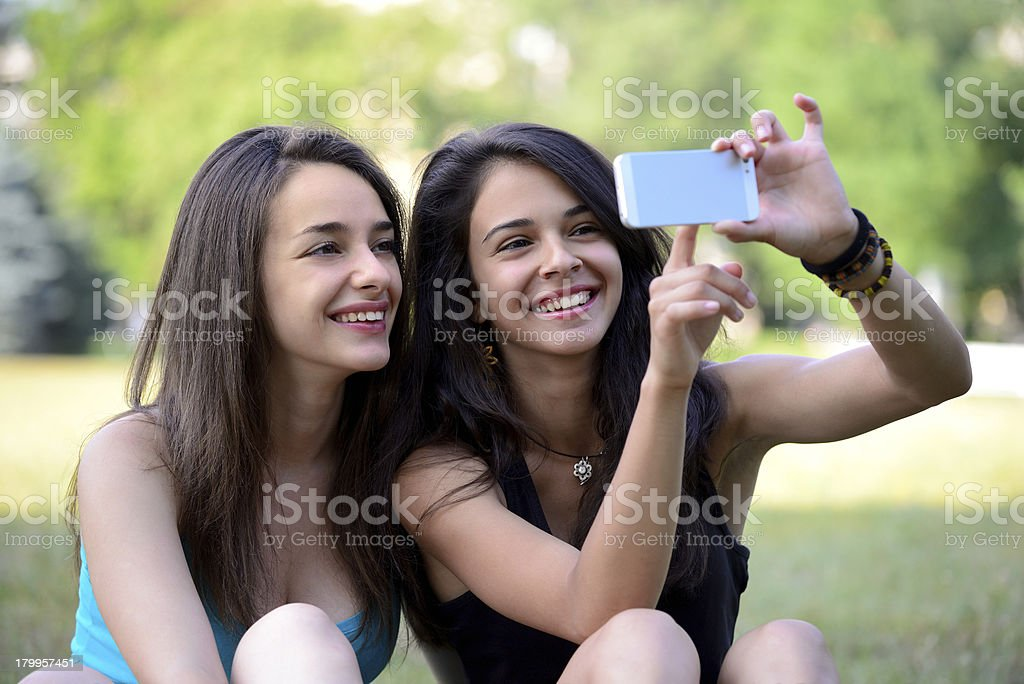 Two Girls Pointing On Smartphone Stock Photo