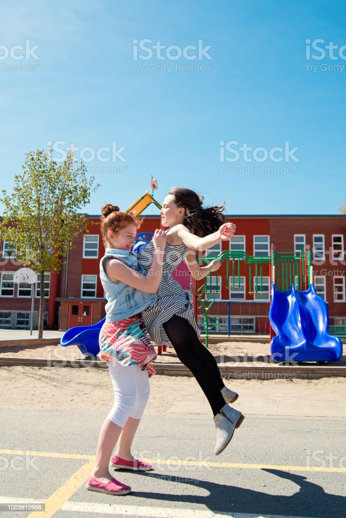 Two girls practicing acrobatics moves in school playground at recess.. stock photo