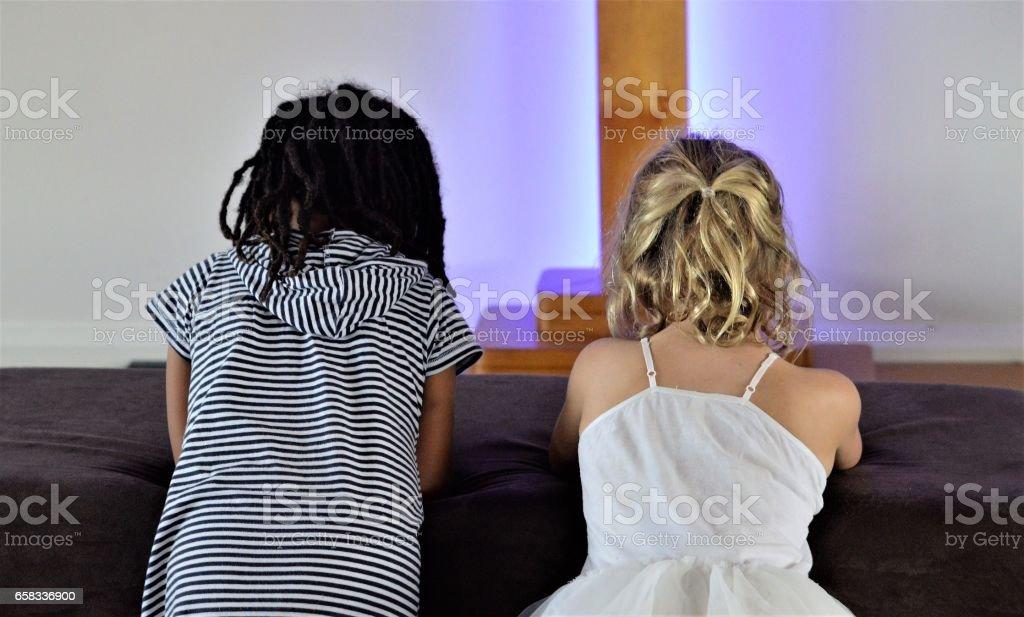 Duas garotas rezam ao pé da Cruz - foto de acervo