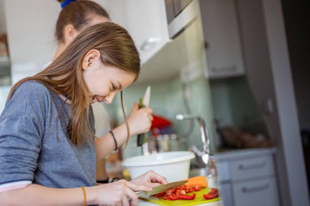 Zwei Mädchen bereiten Essen in einer häuslichen Küche – Foto