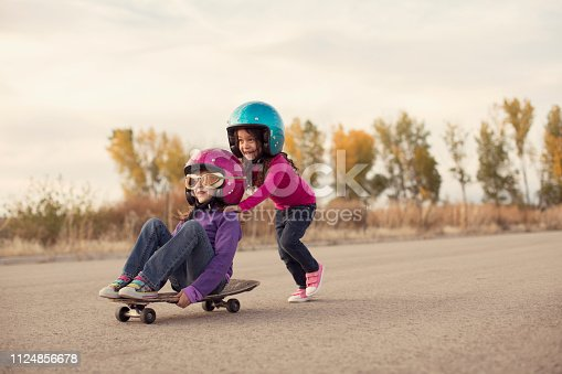 Two young girls are racing on a skateboard. One girl is pushing the other and they are going really fast on a rural road. They are young adventurers wearing helmets and flight goggles and are ready to beat all the boys in the race. Image taken in Utah, USA.