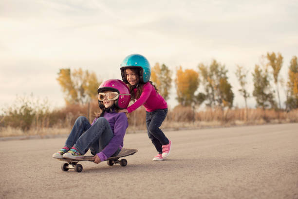 two girls racing on a skateboard - spingere foto e immagini stock