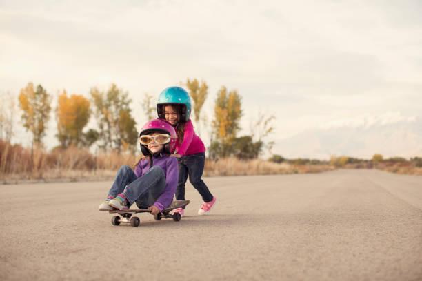 Zwei Mädchen auf einem Skateboard Rennen – Foto
