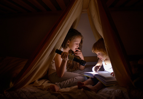 Two girls read fairy tales at dark night under a blanket by the light of a small lamp