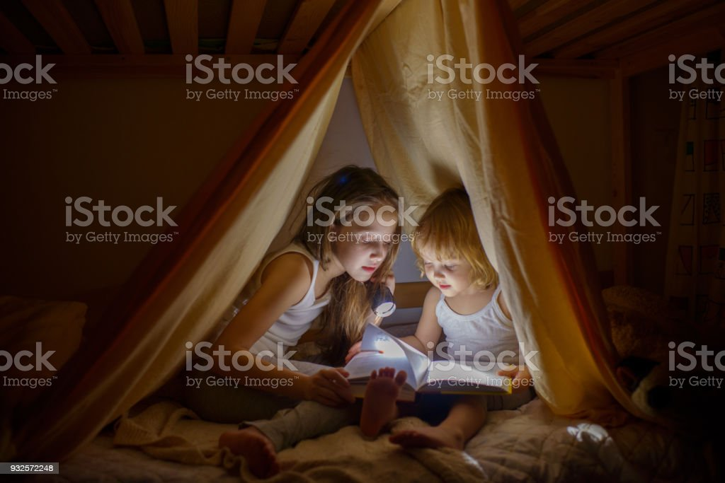 Two girls read fairy tales at dark night under a blanket by the light of a small lamp stock photo