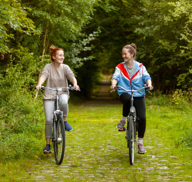 Two girls riding a bike together, outdoors in the forest stock photo
