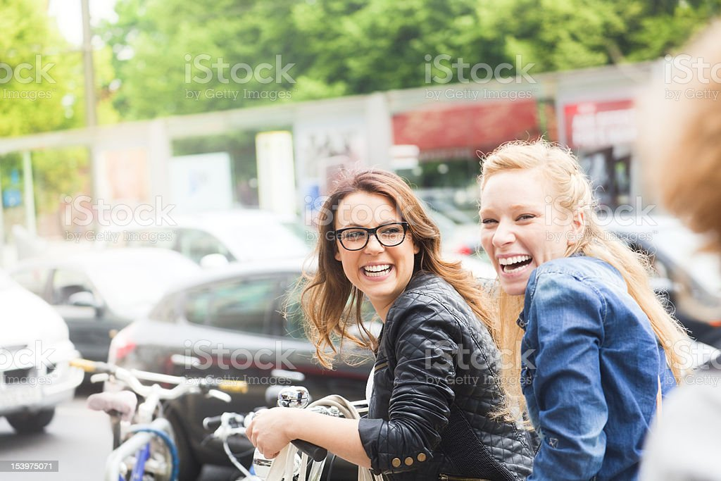 Two girls riding on a bicycle royalty-free stock photo
