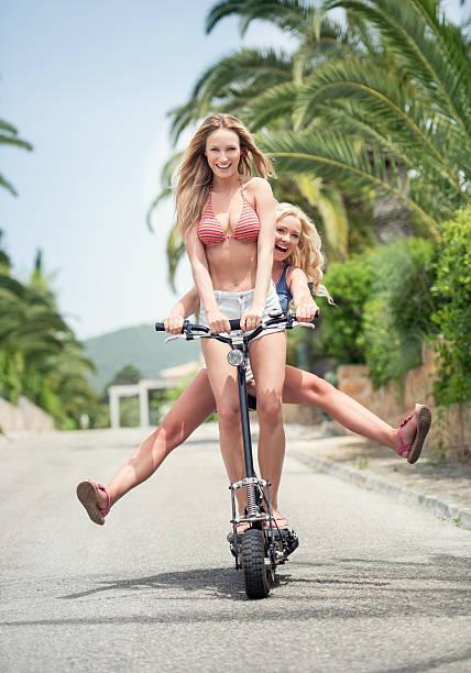zwei mädchen reiten auf ein elektrischer rollstuhl - venice beach in kalifornien stock-fotos und bilder