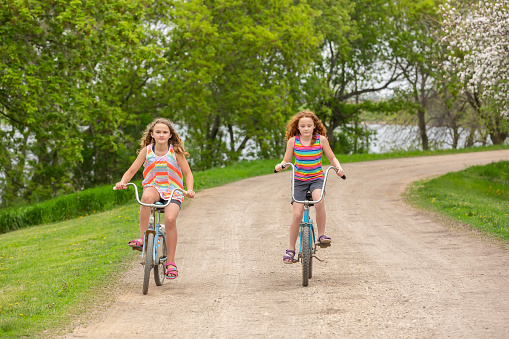 Two Girls Riding Vintage Bikes On Rural Driveway