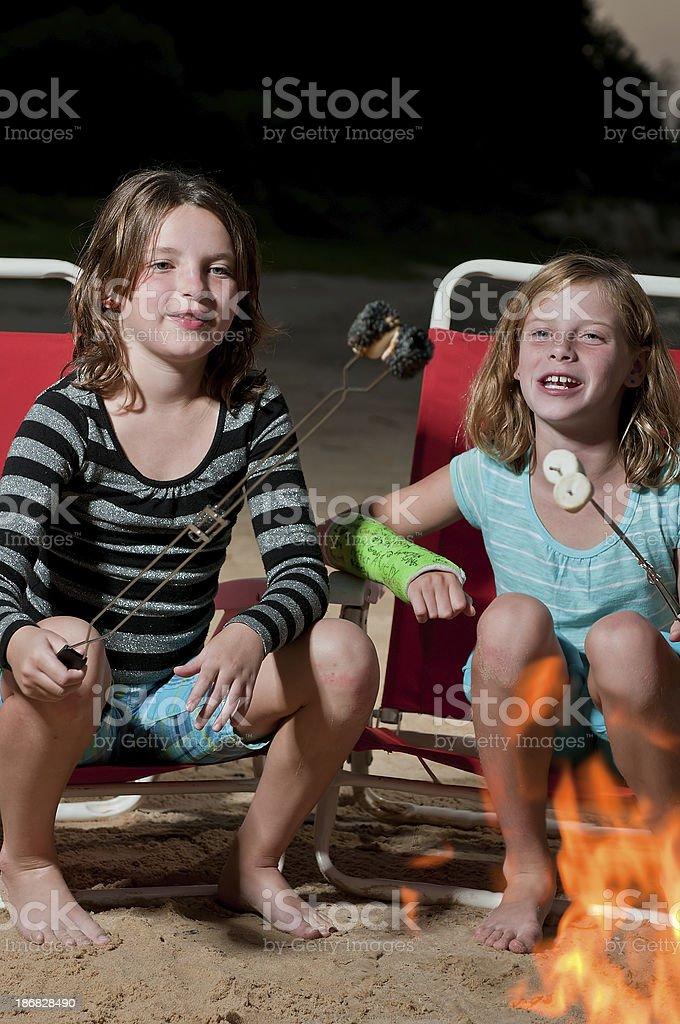 Two girls roasting marshmallows royalty-free stock photo
