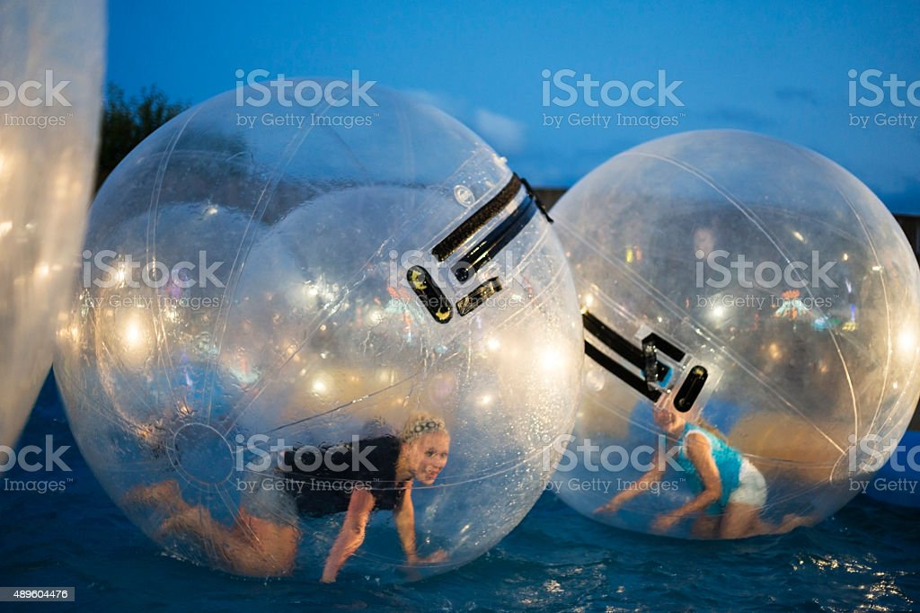 Two girls roll inside giant plastic balls stock photo