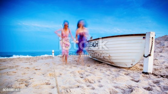 Two girls running at the Jones Beach at the sunset. Blurred picture (motion blur)