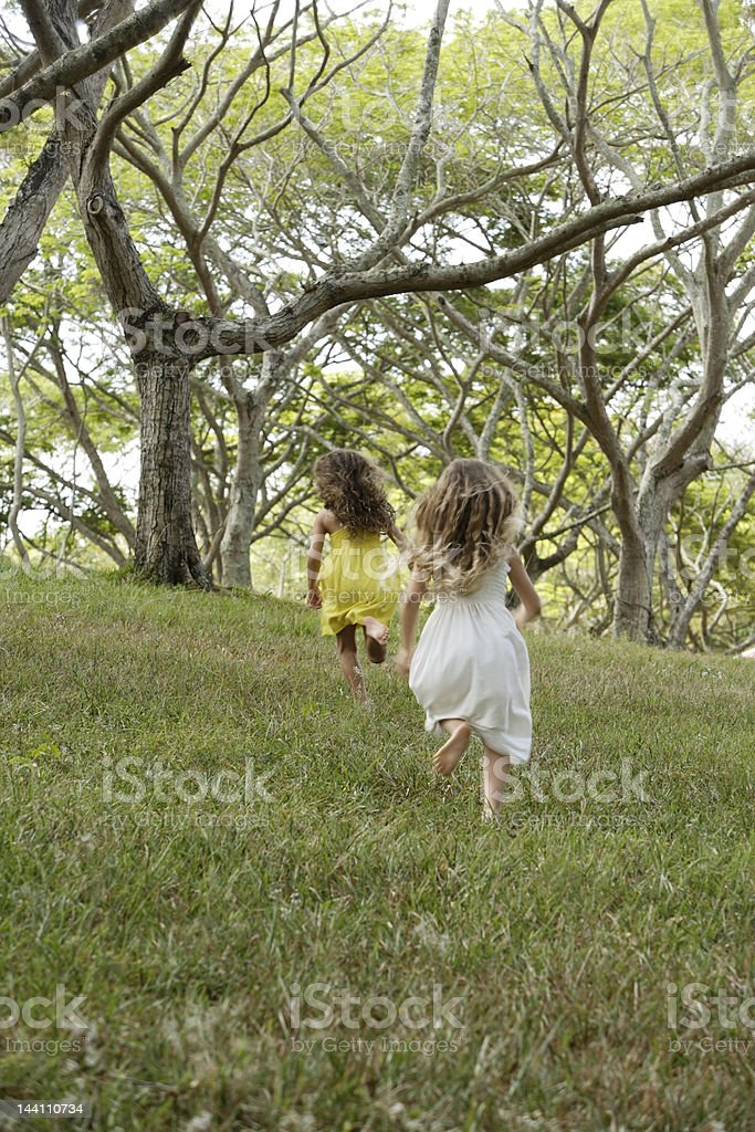 two girls running away through woods stock photo