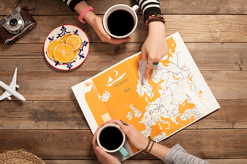 two girls searching their holiday travel with world map