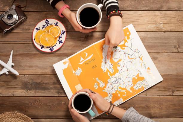 zwei mädchen suchen ihren urlaub reisen mit weltkarte - schönste reiseziele der welt stock-fotos und bilder