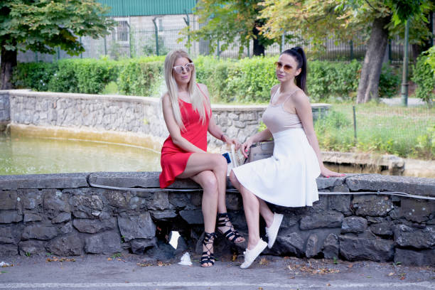 Two girls seating on a bench in the park and posing for a shoot stock photo