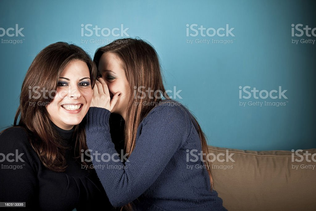 Two girls sharing a secret royalty-free stock photo