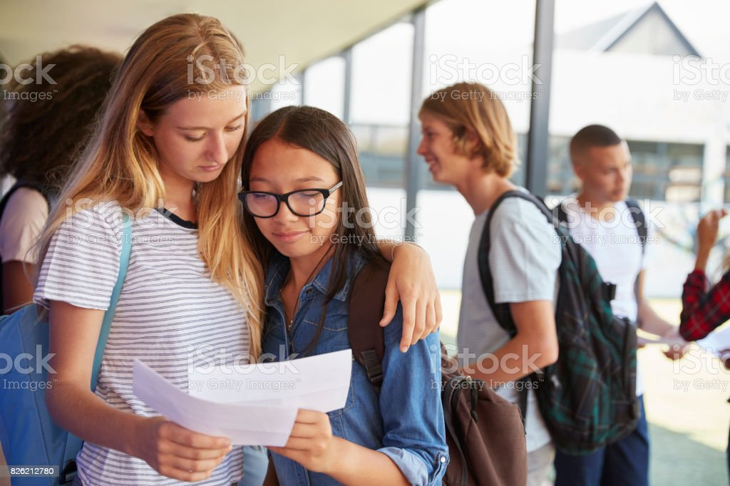 Two girls sharing exam results in school corridor stock photo