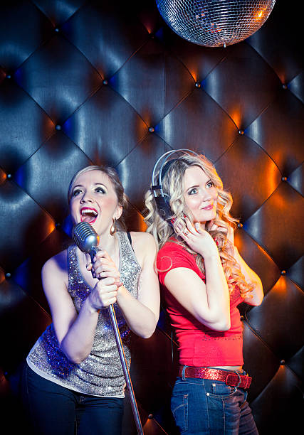 Two girls singing stock photo