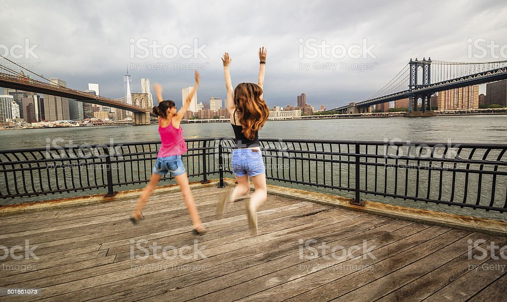 Two girls, sisters, jumping at the waterfront royalty-free stock photo