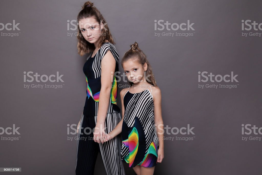 two girls sisters side by side on a grey background stock photo