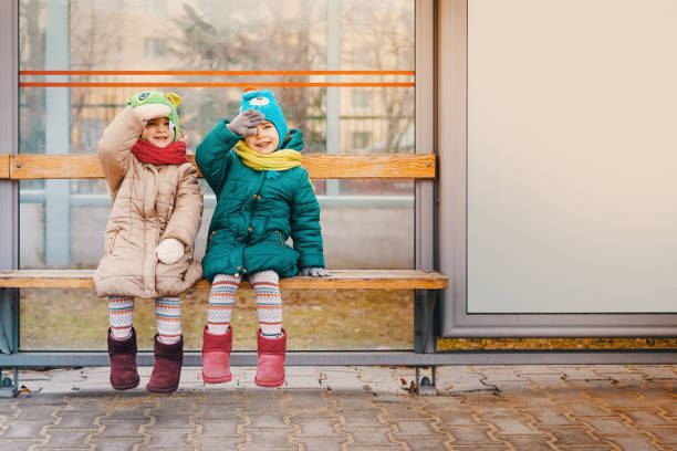 Two girls sit at the bus stop
