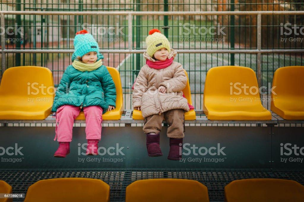 Two girls sit on a tribune stock photo