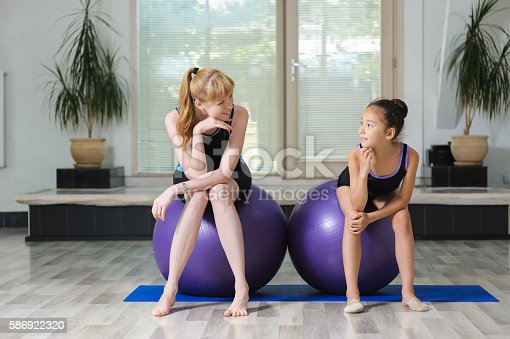 466808392 istock photo Two girls sit on gymnastic balls in gym 586922320