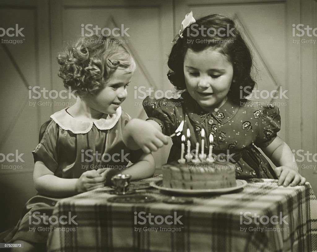 Two girls (3-4), (4-5) sitting at small table with birthday cake, (B&W) stock photo