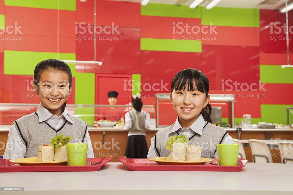 Two girls sitting in school cafeteria royalty-free stock photo