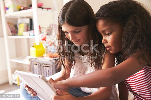 istock Two Girls Sitting On Bed Using Digital Tablet Together 807406222