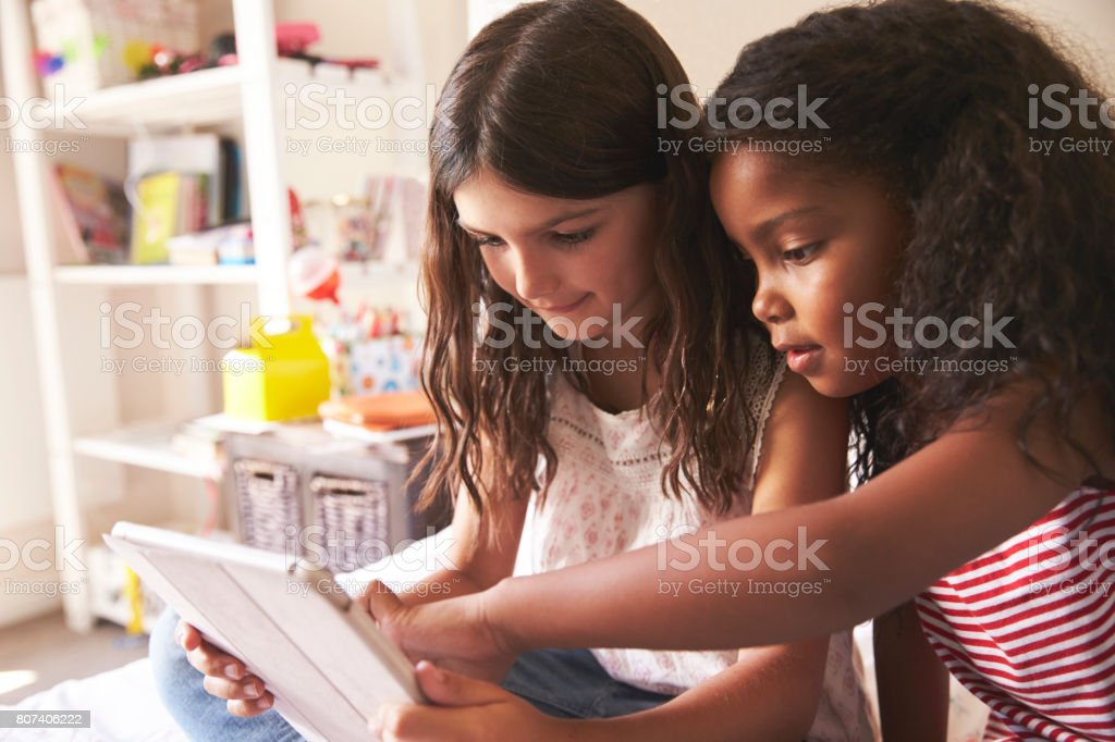 Two Girls Sitting On Bed Using Digital Tablet Together stock photo