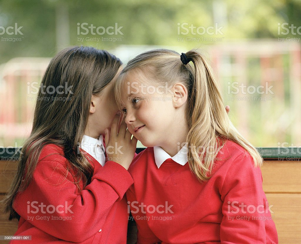 Two girls (6-8) sitting on bench whispering, close-up stock photo
