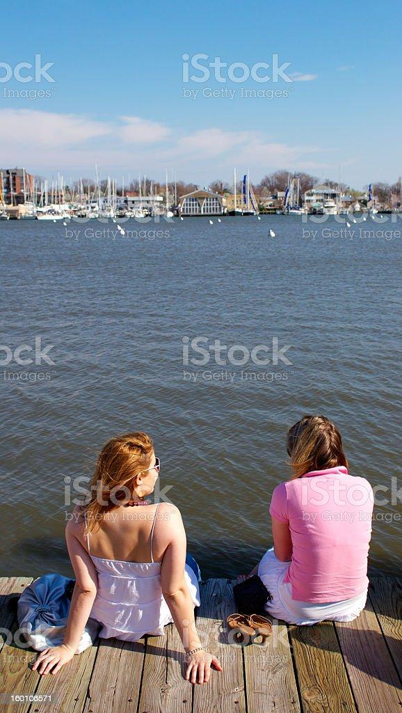 Two girls sitting on boardwalk royalty-free stock photo